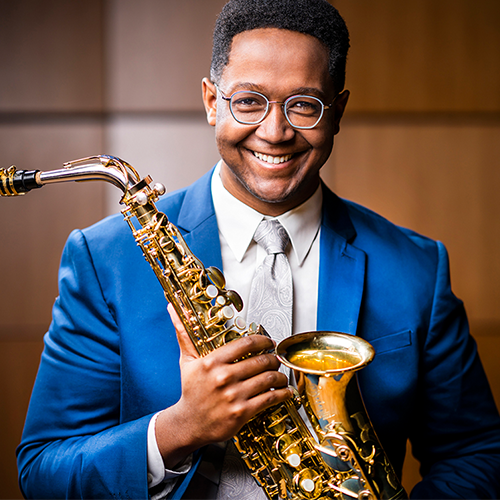 Smiling Saxophone player wearing glasses and blue suit