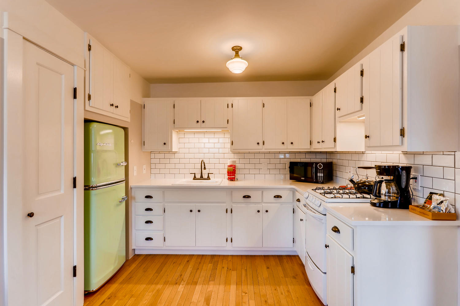 kitchen with white cabinets, tile and green refridgerator