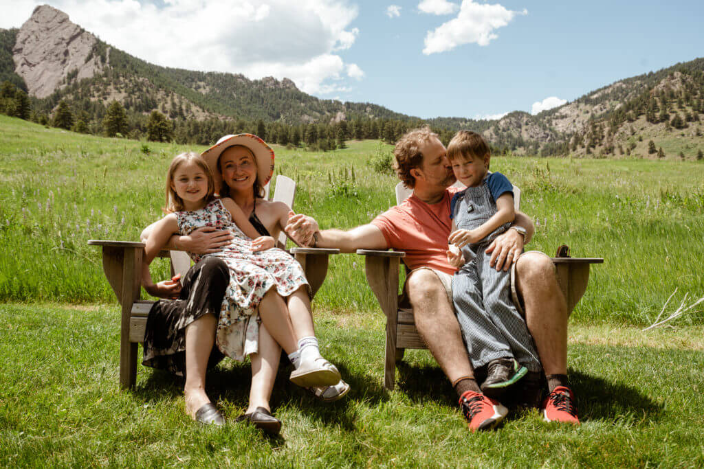 Family sitting in lounge chairs in front of Boulder Flatirons mountains